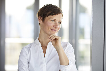 Portrait of smiling businesswoman in office looking sideways - RBF06368