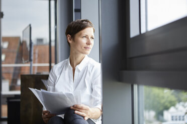 Businesswoman sitting in office with documents looking out of window - RBF06380