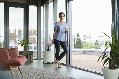 Portrait of woman at home with cup of coffee standing at balcony door - RBF06386
