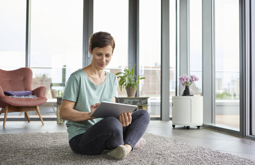 Woman sitting on the floor at home using tablet - RBF06389