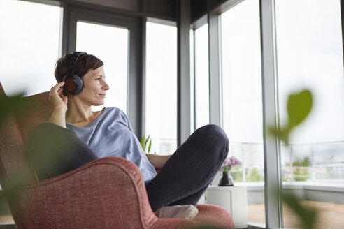 Woman sitting in armchair at home listening to music with headphones - RBF06395