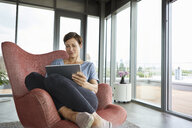 Woman sitting in armchair at home using tablet - RBF06398