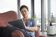 Woman sitting in armchair at home using tablet - RBF06401