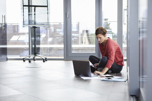 Businesswoman sitting on the floor in office using laptop - RBF06404