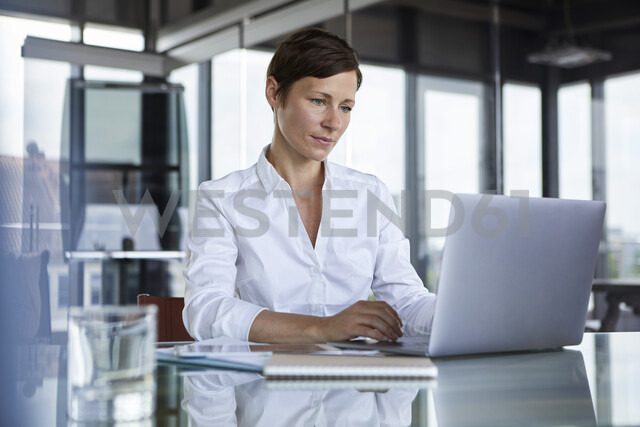 Businesswoman sitting at glass table in office using laptop - RBF06407 - Rainer Berg/Westend61