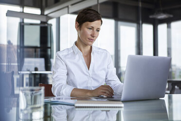 Businesswoman sitting at glass table in office using laptop - RBF06407