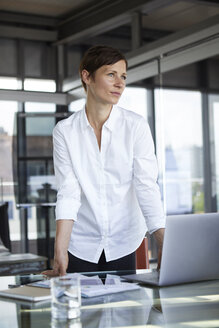 Businesswoman standing at glass table in office with laptop looking sideways - RBF06410