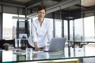 Portrait of confident businesswoman standing at glass table in office with laptop - RBF06413