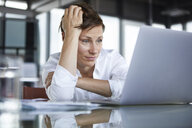 Frustrated businesswoman sitting at glass table in office looking at laptop - RBF06416