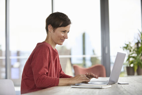 Smiling woman sitting at table at home using laptop - RBF06419