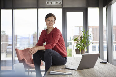 Portrait of confident woman sitting on table at home with laptop - RBF06422