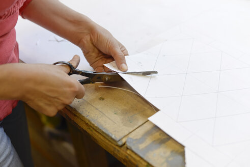 Close-up of woman cutting paper from draft in glazier's workshop - BFRF01863