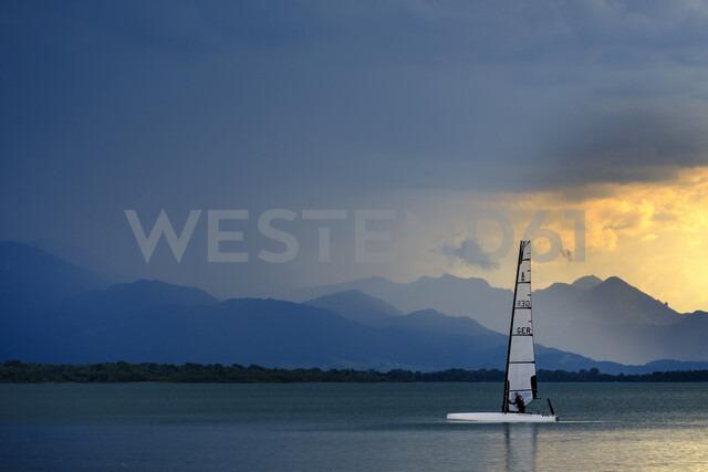 Germany, Bavaria, Chiemgau Alps, Chieming at Chiemsee, dark clouds over Lake Chiemsee, sailing boat - LBF01989