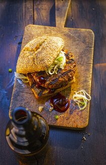 Burger on wooden board next to beer bottle - KSWF01927