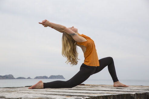 Mid adult woman bending backwards practicing yoga on wooden sea pier - CUF38113