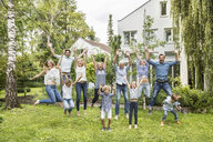Three generational family jumping in garden - CUF38200