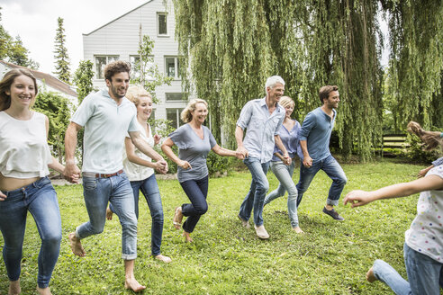 Two generational family running in garden - CUF38206