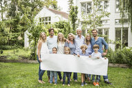Three generational family in garden with blank banner - CUF38209