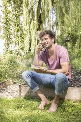 Young man in garden on cell phone with plate of food - CUF38236