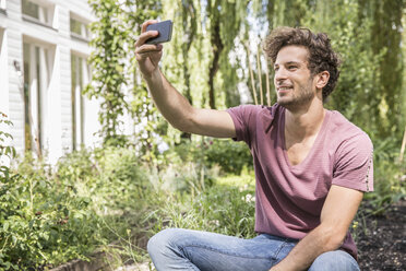 Young man taking selfie with cell phone in garden - CUF38239