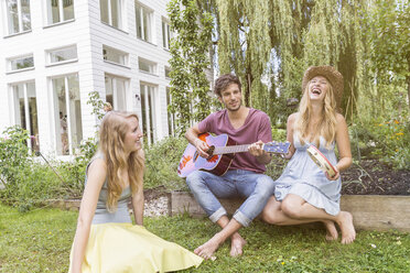 Three friends in garden, man playing guitar - CUF38242