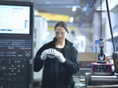 Mid adult female engineer inspecting part in factory - CUF38248