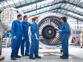 Group of engineers working on engine in aircraft maintenance factory - CUF38311