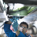 Engineer working on aircraft wing in aircraft maintenance factory, close up - CUF38317