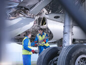 Engineers recycling aircraft parts from airplane on runway - CUF38326