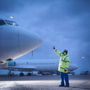 Airport worker guiding aircraft on runway at night - CUF38329