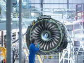 Engineer inspecting jet engine in aircraft maintenance factory - CUF38338