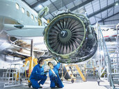 Aircraft engineers inspecting jet engine in aircraft maintenance factory - CUF38341