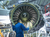 Engineer inspecting jet engine in aircraft maintenance factory - CUF38344