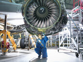Engineer inspecting jet engine in aircraft maintenance factory - CUF38347