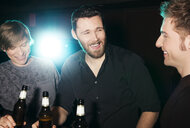 Three male friends drinking bottled beer in nightclub - CUF38398