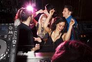 Group of friends dancing in front of  DJ in nightclub - CUF38404