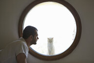 Mid adult man gazing at cat through circular window - CUF38413