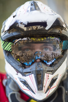 Close up portrait of male motocross racer wearing muddy helmet and goggles - CUF38539
