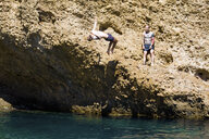 Two young men diving into sea from rocks, Marseille, France - CUF38545