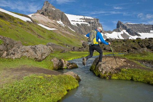 Hiker jumping over little river at Dyrfjoll Mountain range, East Iceland, Iceland - CUF38593