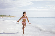 Girl running on beach, Tuscany, Italy - CUF38602