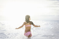 Rear view of girl running and splashing in sea, Tuscany, Italy - CUF38605