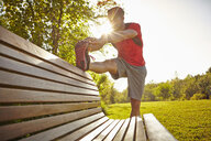 Young male runner stretching legs on park bench - ISF15371