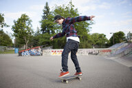 Young man skateboarding in city skateboard park - ISF15395
