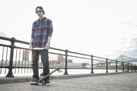 Portrait of young male skateboarder on waterfront - ISF15401