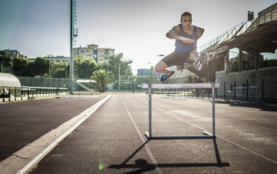 Mid adult man jumping over hurdle - ISF15560