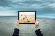 Mature woman on cloudy beach, holding digital tablet showing sunny beach scene, focus on hands and laptop - CUF38654