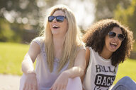 Two young female friends laughing in park - CUF38672