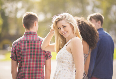 Young woman with friends in park looking over her shoulder - CUF38681