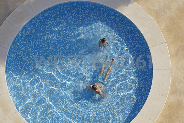 Overhead view of man and toddler daughter in swimming pool - CUF38690